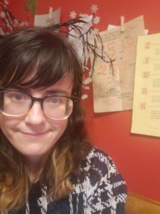 Woman wearing glasses smiling in front of a red wall with broadsides taped up behind her.